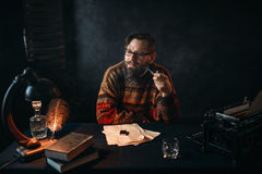 Bearded writer in glasses smoking a pipe. Thoughtful bearded writer in glasses smoking a pipe and look at the window. Retro typewriter, feather, crystal decanter Stock Photos