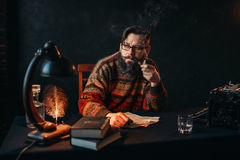 Bearded writer in glasses smoking a pipe. Thoughtful bearded writer in glasses smoking a pipe and look at the window. Retro typewriter, feather, crystal decanter Royalty Free Stock Image