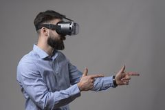 Bearded young adult man wearing vr headset with finger gun gesture simulate shooting augmented reality weapon. Over gray studio background royalty free stock image