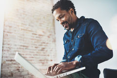 Bearded young African man smiling and using laptop while sitting at his modern coworking place.Concept of happy business. People.Blurred background, flare Royalty Free Stock Images