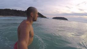 Bearded young athletic man walk into the sea and dive under waves. Gopro HD sunset selfie. Phuket, Thailand. stock video footage