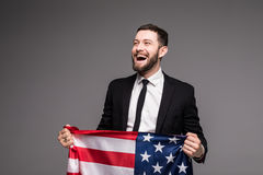 Bearded young Business man in suit holding USA flag and looking up isolated gray background Royalty Free Stock Photos