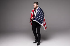Bearded young Business man in suit holding USA flag and looking up isolated gray background Stock Image