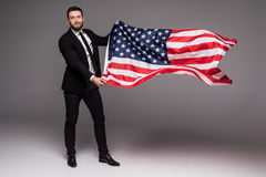 Bearded young Business man in suit holding USA flag and looking up isolated gray background Stock Photography