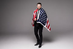 Bearded young Business man in suit holding USA flag and looking up isolated gray background Stock Images