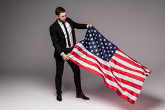 Bearded young Business man in suit holding USA flag and looking up isolated gray background Royalty Free Stock Photography