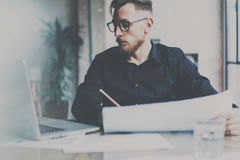 Bearded young businessman in eyeglasses working on modern office.Man using contemporary laptop and making notes on. Document.Horizontal, film effect.Blurred stock photos