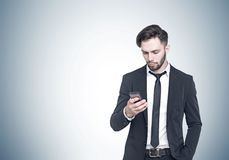 Bearded young businessman looking at smartphone Stock Images