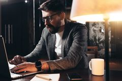Bearded young businessman working in loft space at night. Coworker sits by the wooden table with lamp and office tools. Project manager using contemporary royalty free stock photo