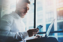 Bearded young businessman working on modern loft.Man wearing white shirt and using contemporary laptop,smartphone. Panoramic windows background. Horizontal Royalty Free Stock Photography