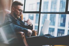 Bearded young businessman working on modern loft office. Man sitting in vintage chair, holding glass water. Using. Bearded young businessman working on modern stock photos