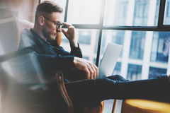 Bearded young businessman working on modern loft office. Man sitting in vintage chair. Using contemporary notebook Royalty Free Stock Image