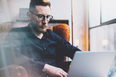 Bearded young businessman working on modern loft office. Man sitting in vintage chair. Using contemporary notebook Royalty Free Stock Photos