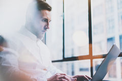 Bearded young businessman working on modern loft office. Man wearing white shirt and using contemporary laptop. Panoramic windows background Royalty Free Stock Photos