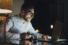 Bearded young businessman working on modern loft office at night. Man using contemporary notebook texting message. Holding smartphone, blurred background stock photography