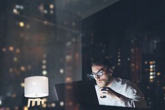 Bearded young businessman working on modern loft office at night. Man using contemporary notebook texting message, holding cup esp Royalty Free Stock Photo