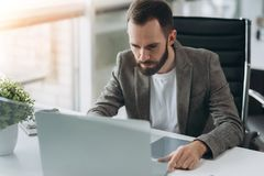 Bearded young businessman working at modern office.Man wearing white shirt and making notes on the documents.Panoramic windows stock photography