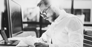 Bearded young businessman working at modern office.Man wearing white shirt and making notes on the documents.Panoramic Royalty Free Stock Images
