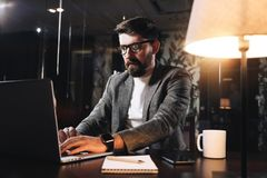 Bearded young businessman working on open space office at night. Man using modern notebook, typing text. Coworker working stock images