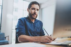 Bearded young businessman working at sunny office.Man using contemporary laptop and making notes document.Horizontal Stock Photos