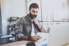 Bearded young businessman working at sunny office.Man using contemporary laptop and making notes in notebook.Horizontal. Blurred background Stock Images