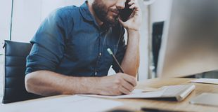 Bearded young businessman working at sunny office.Man using contemporary smartphone and making notes document.Horizontal Stock Photo
