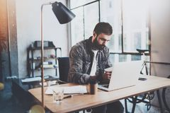 Bearded young coworker working at sunny office.Man using contemporary laptop and making notes in notebook.Horizontal. Blurred background Royalty Free Stock Photography