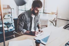 Bearded young coworker working at sunny studio .Man using contemporary laptop and making notes in notebook.Horizontal. Blurred background Stock Photos