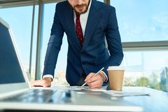 Stylish Entrepreneur Concentrated on Work. Bearded young entrepreneur in stylish suit leaning on desk while taking necessary notes, interior of spacious office Stock Photo