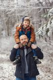 Bearded young father and l little son on walk in winter forest. Boy sits in man shoulders. Christmas vacation stock photography