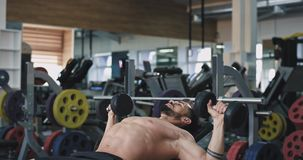 A bearded young fit man , works on his biceps and triceps while lifting two mini weights. 4k stock footage