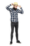 Bearded young hipster adjusting straw hat visor looking away Royalty Free Stock Image