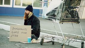 Bearded young homeless man with cardboard sitting near shopping cart and drink alcohol at cold day. Immigrants crisis in. Bearded young homeless man with Royalty Free Stock Image