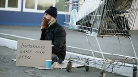 Bearded young homeless man with cardboard sitting near shopping cart and drink alcohol at cold day. Immigrants crisis in stock footage