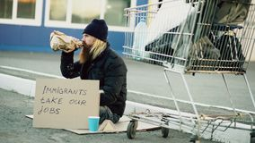 Bearded young homeless man with cardboard sitting near shopping cart and drink alcohol at cold day. Immigrants crisis in. Bearded young homeless man with Stock Image
