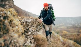 Bearded young male hiking in mountains with travel backpack. Traveler man trekking during his journey. Travel, people, healthy lifestyle concept royalty free stock photos