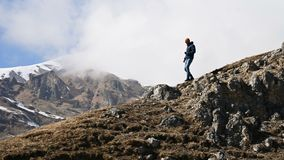 Bearded young male photographer in a hat and sunglasses and a camera around his neck climbs up the hill against the stock video