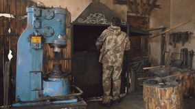 Bearded young man blacksmith using hydraulic press for steel arms manufacture at smithy workshop stock video