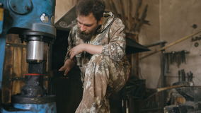 Bearded young man blacksmith using industrial press for steel arms manufacture at smithy workshop stock video