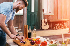 Bearded young man cutting onion for barbecue Stock Images