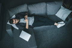 Bearded young man in eyeglasses and earphones using smartphone while lying on sofa. High angle view of bearded young man in eyeglasses and earphones using Royalty Free Stock Photo