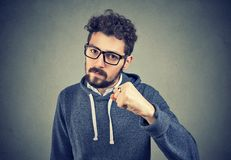 Aggressive man threatening with fist. Bearded young man in glasses holding fist up looking serious and with threat on gray background Stock Photo