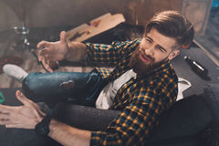 Bearded young man with hangover gesturing in messy room after party Stock Image