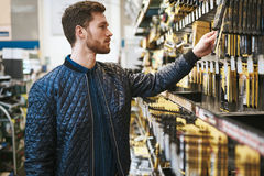 Bearded young man in a hardware store. Standing reading the information on a product hanging on the rack, side view close up Stock Photography