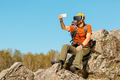 Bearded young man makes selfie in glasses virtual reality outdoors. Bearded young man, makes selfie, in glasses virtual reality, outdoors the mountains royalty free stock image