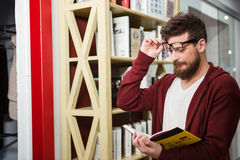 Bearded young man reading book standing near the bookshelf Stock Photography