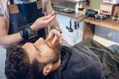 Bearded young man ready for shaving in the hair salon of a skilled barber. Side view headshot of a redhead bearded young men smiling, ready for shaving in the Royalty Free Stock Photo