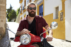 Bearded young man sitting on motor scooter, Ibiza, Spain Stock Photography