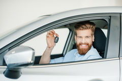 Bearded young man sitting in new car and holding key Stock Photos