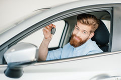Bearded young man sitting in new car and holding key Stock Photo